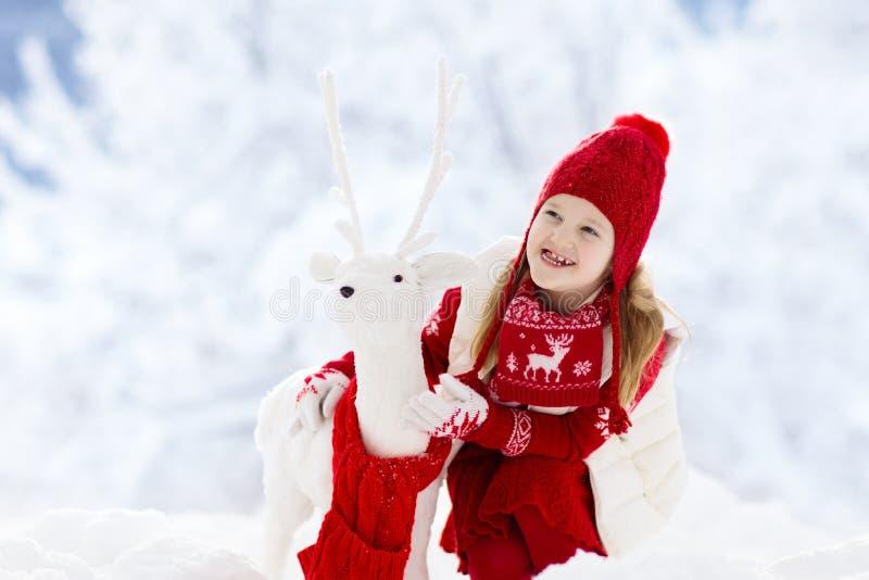 Criança que joga na neve no Natal Miúdos no inverno fotografia de stock royalty free