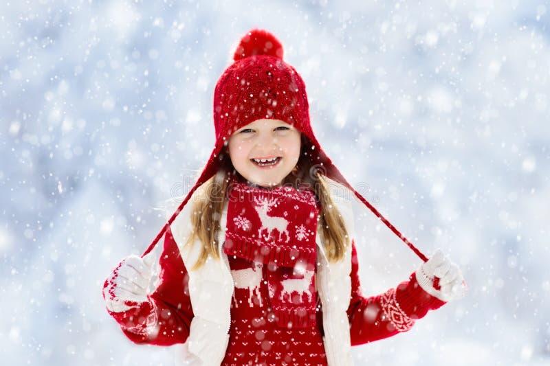 Criança que joga na neve no Natal Miúdos no inverno fotografia de stock
