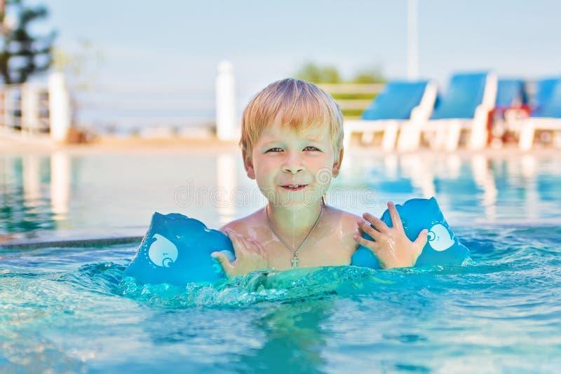 Criança que joga na piscina imagem de stock