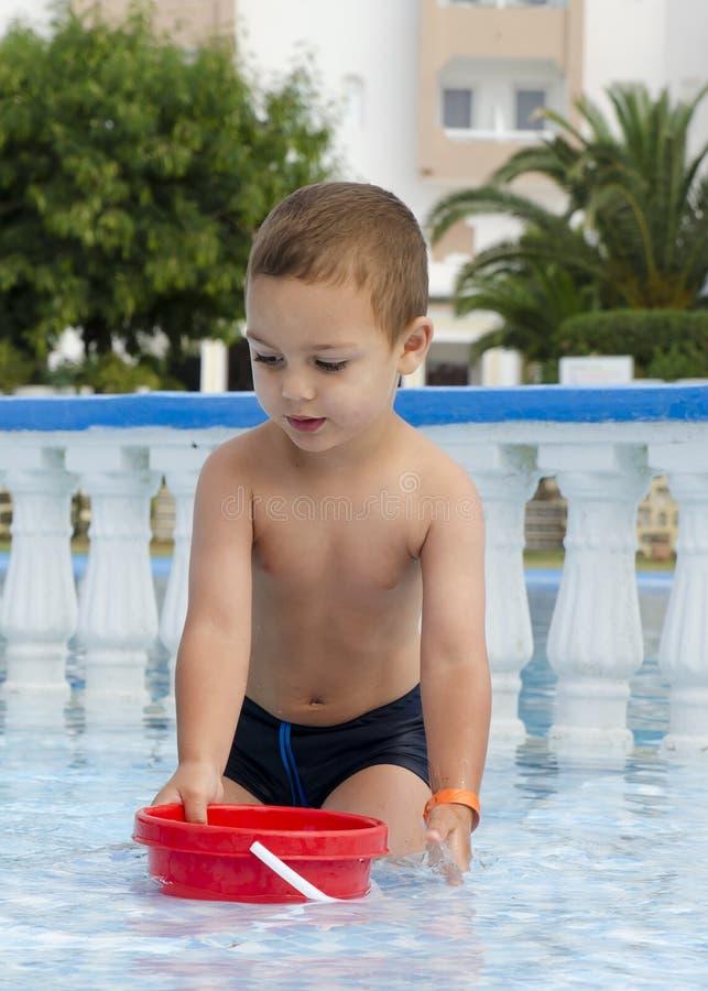 Criança que joga na piscina foto de stock