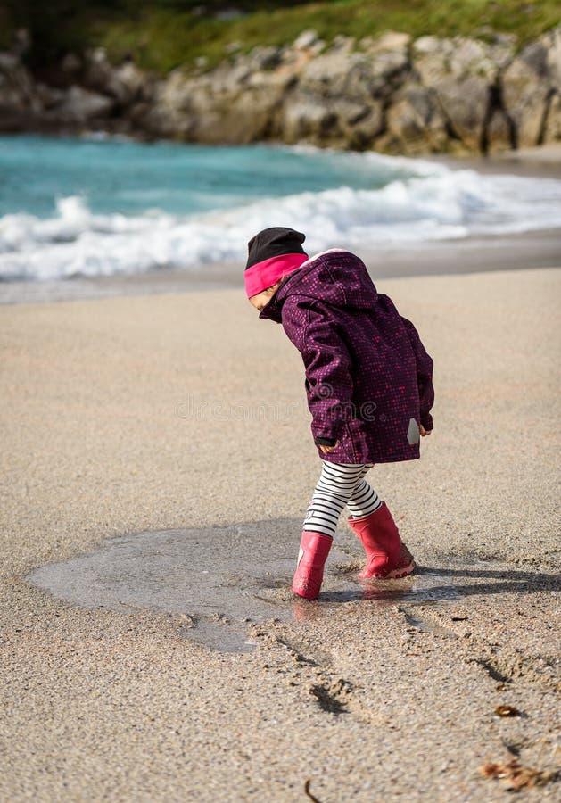 Criança que joga na poça no Sandy Beach de Oceano Atlântico imagem de stock