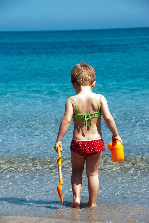 Criança que joga na praia foto de stock
