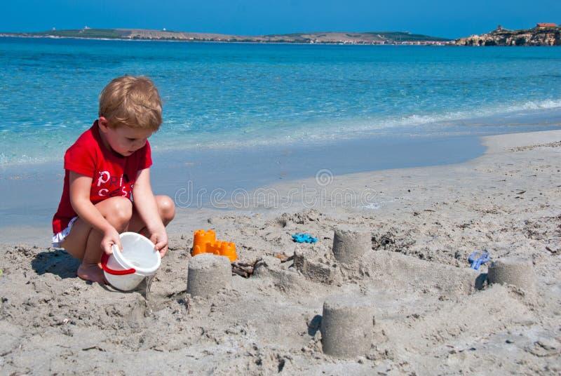 Criança que joga na praia foto de stock royalty free
