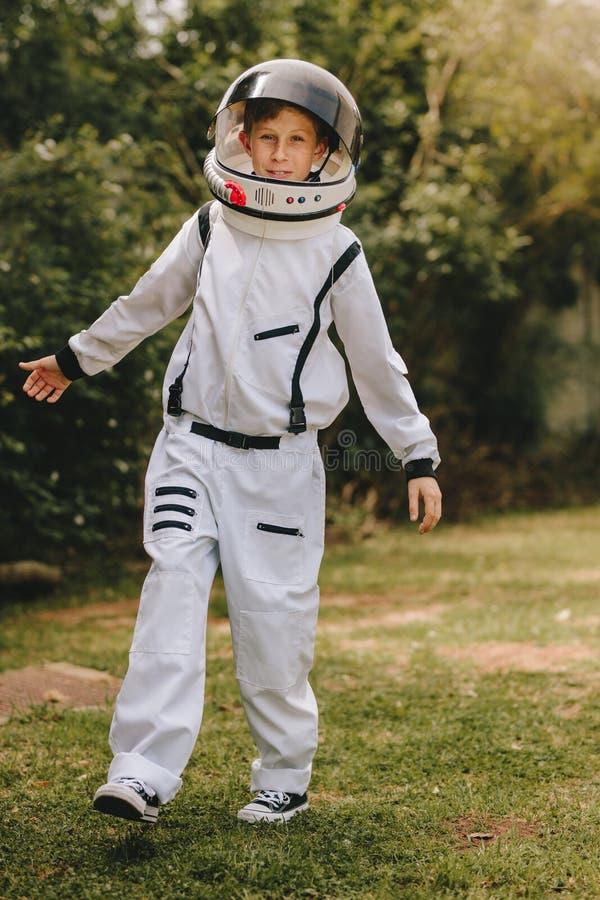 Criança que joga no terno do astronauta fora fotografia de stock royalty free