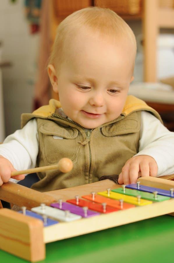 Criança que joga no xylophone imagem de stock