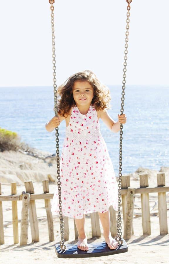 Criança que joga o balanço em férias foto de stock royalty free