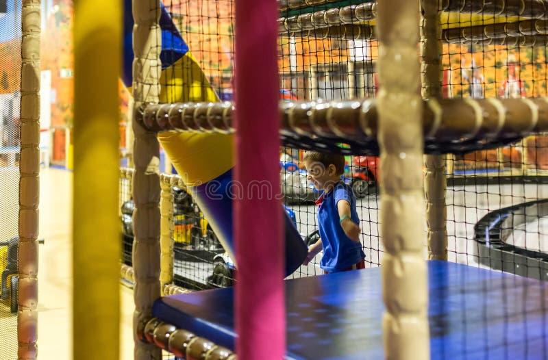 Criança que joga o campo de jogos interno fotografia de stock