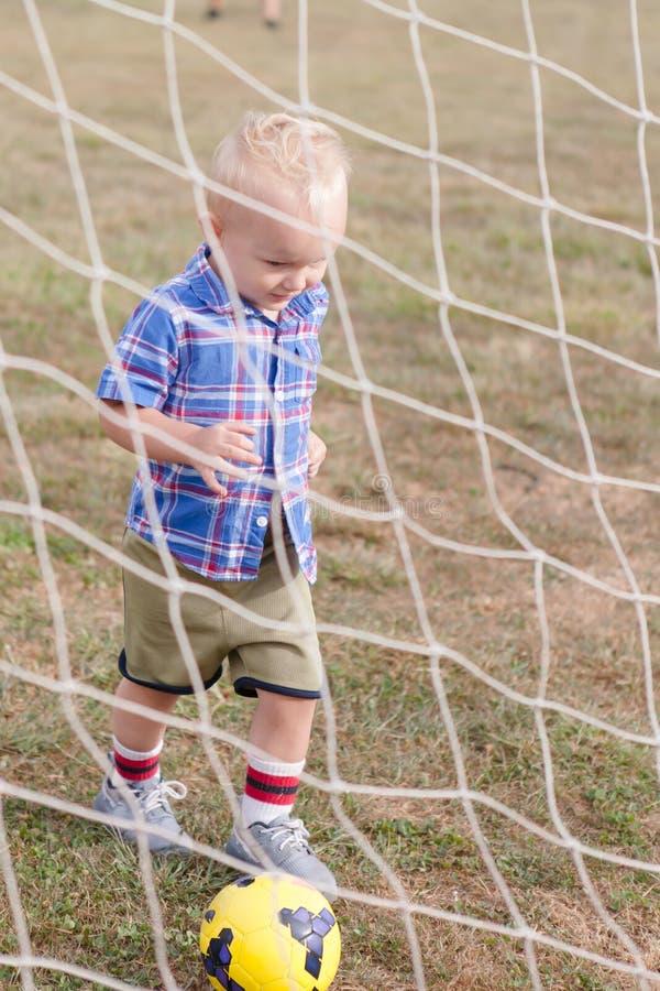 Criança que joga o futebol fotografia de stock