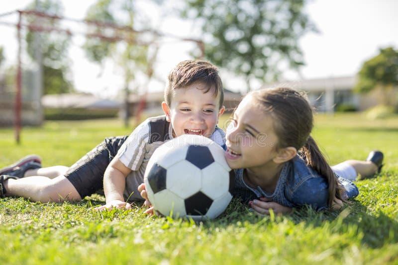 Criança que joga o futebol no campo com irmã fotos de stock