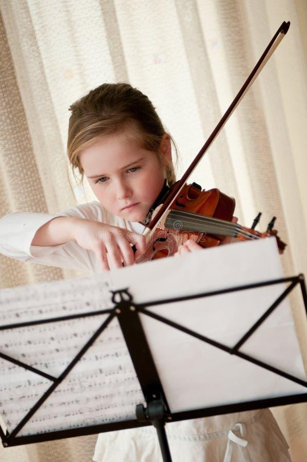 Criança que joga o violino em casa imagens de stock