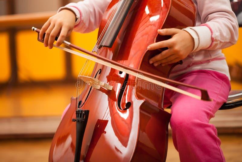 Criança que joga o violoncelo fotografia de stock royalty free