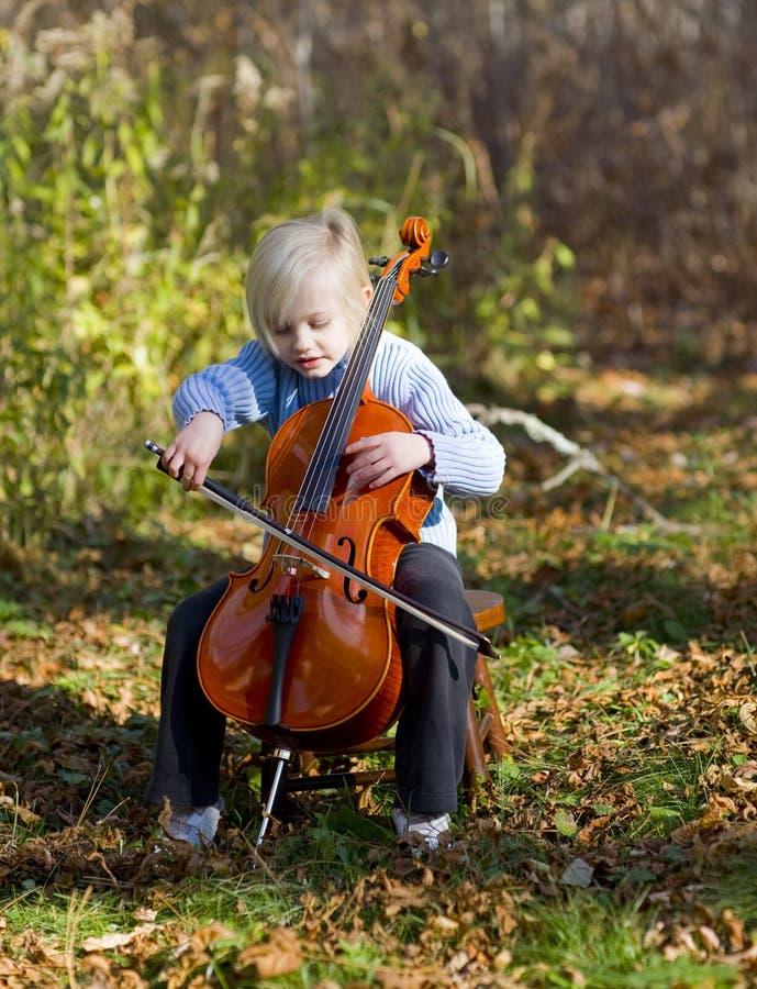 Criança que joga o violoncelo foto de stock royalty free