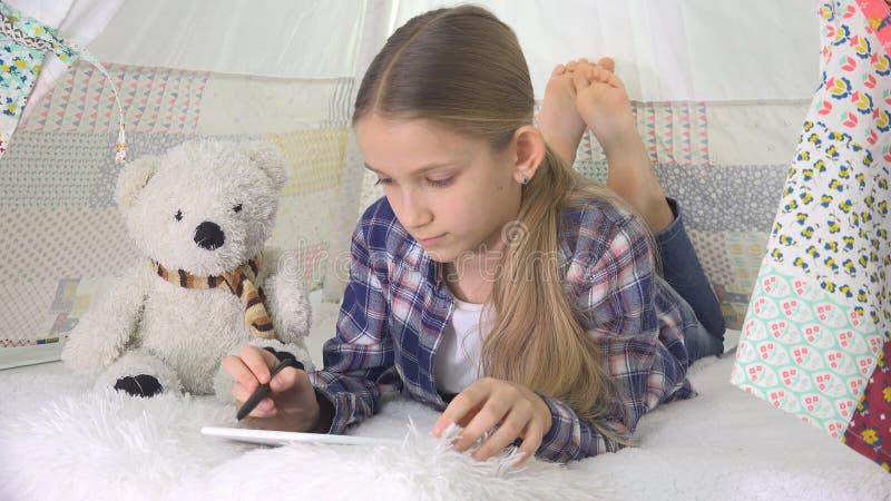 Criança que joga a tabuleta na menina da sala de jogos que escreve trabalhos de casa para o campo de jogos da criança da escola fotos de stock royalty free