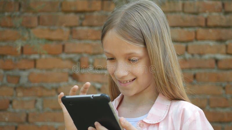 A criança que joga a tabuleta pela parede de tijolos na jarda, menina usa Smartphone exterior fotografia de stock
