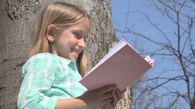 A criança que lê no parque da árvore, estudante lê o livro exterior na natureza, educativa fotos de stock