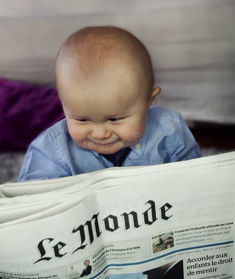 Criança que lê o jornal de Le Monde imagens de stock royalty free