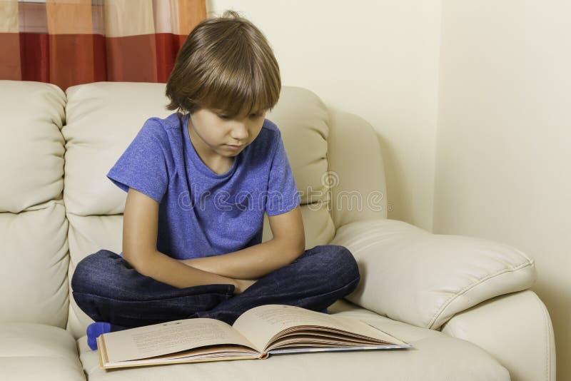 Criança que lê um livro em casa fotografia de stock
