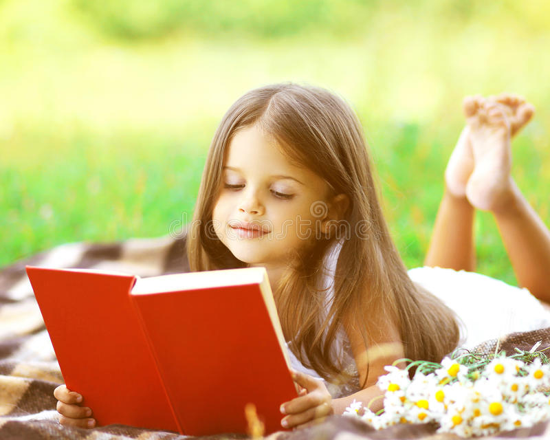 Criança que lê um livro na grama foto de stock royalty free