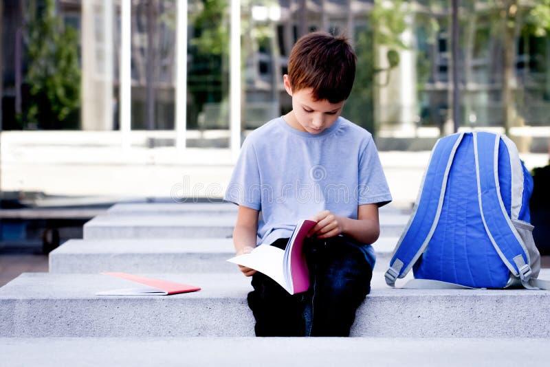 Criança que lança através das páginas do livro Livro de leitura do menino e fazer trabalhos de casa fora imagens de stock