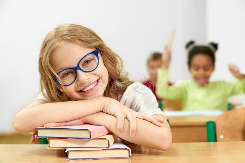 Criança que levanta ao sentar-se na mesa e ao encontrar-se em livros imagem de stock