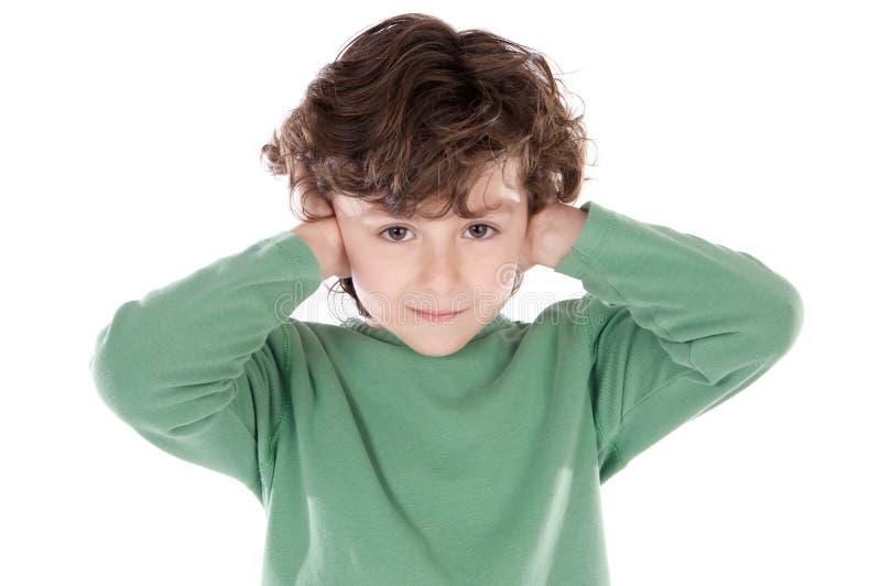 Criança que mantem suas mãos de encontro a suas orelhas fotografia de stock