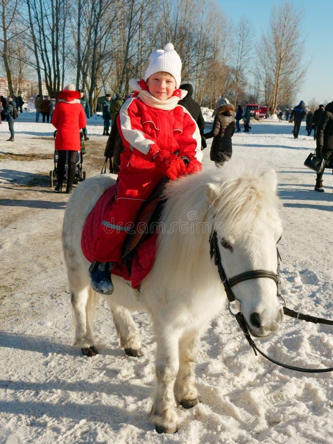 Criança que monta um pônei fora no inverno imagem de stock royalty free