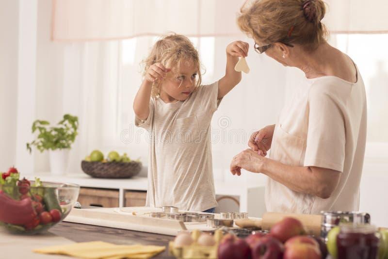 Criança que mostra cookies ao baby-sitter fotos de stock royalty free