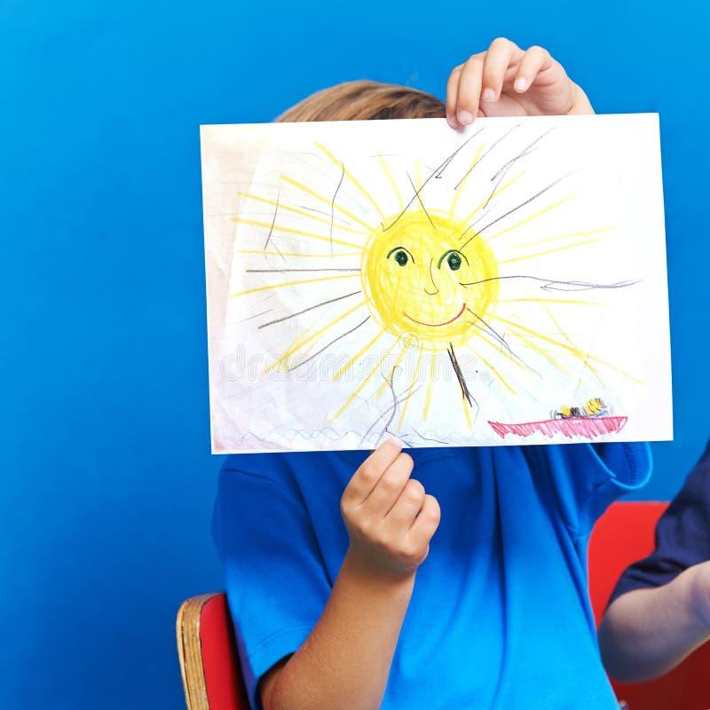 Criança que mostra o desenho com sol e oceano imagens de stock