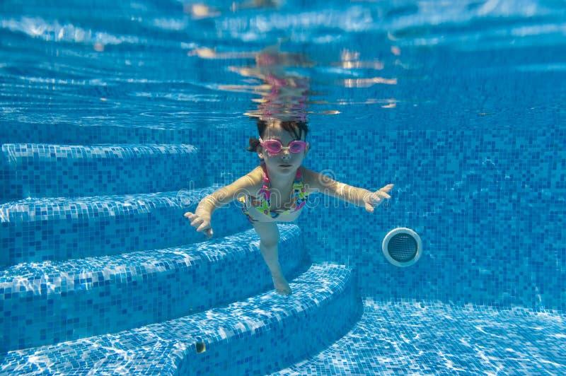 Criança que nada debaixo d'água na associação imagem de stock
