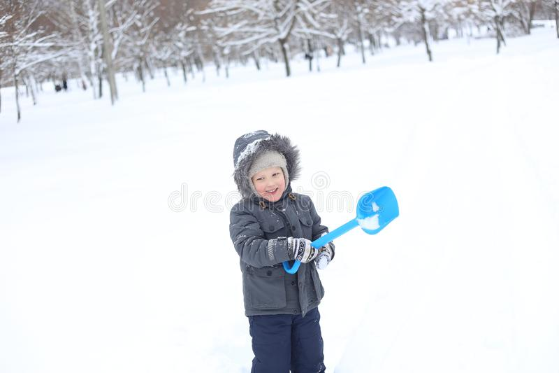 A criança que o revestimento morno joga ativamente a neve exulta fotografia de stock