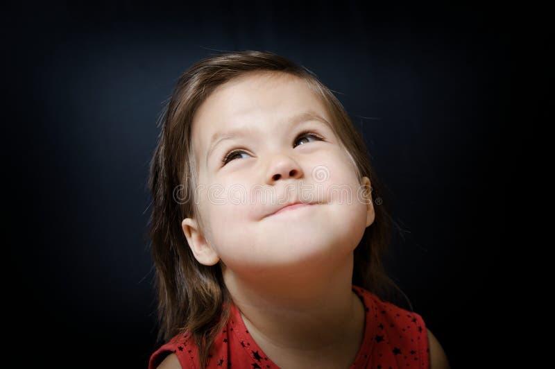 Criança que olha acima no fundo escuro menina que sorri e que olha com surpresa fotografia de stock