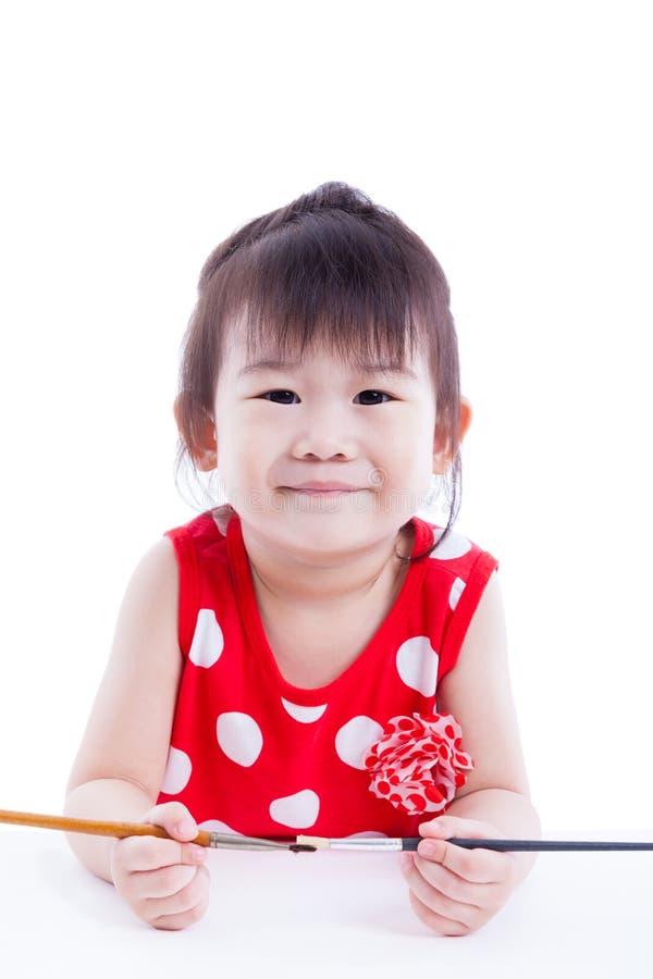 Criança que olha a câmera e o sorriso, guardando paintbrushs fotos de stock
