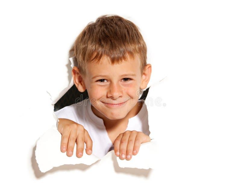 Criança que olha fora de um furo fotos de stock royalty free