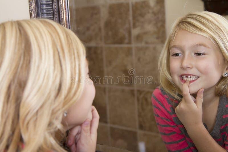 Criança que olha no espelho em faltar o dente anterior foto de stock
