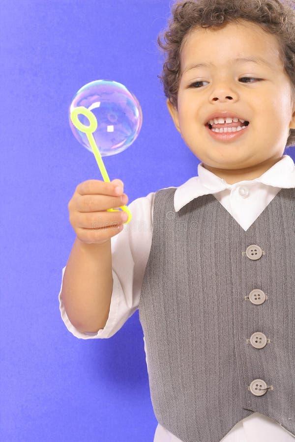 Criança que olha o lado da bolha imagem de stock