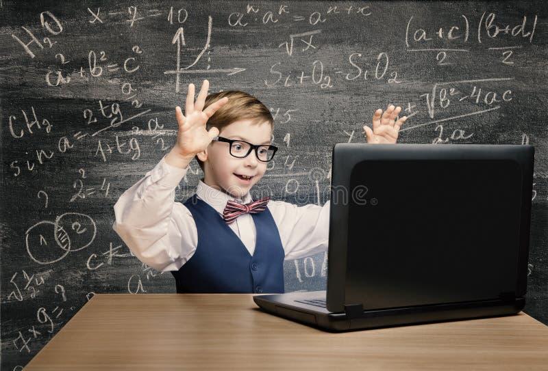 Criança que olha o portátil, criança com caderno, fórmula de Little Boy fotos de stock