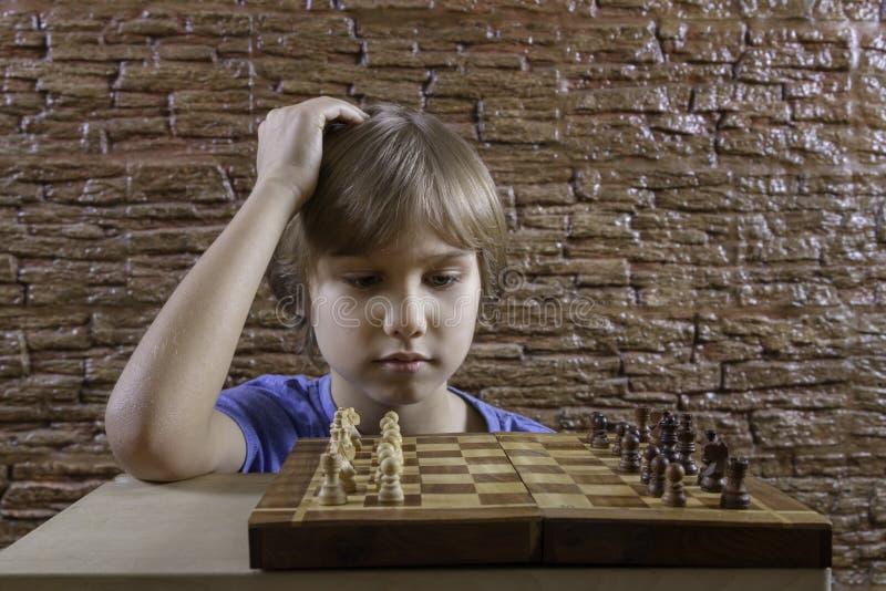 A criança que olha a placa de xadrez e pensa sobre o jogo novo fotos de stock royalty free
