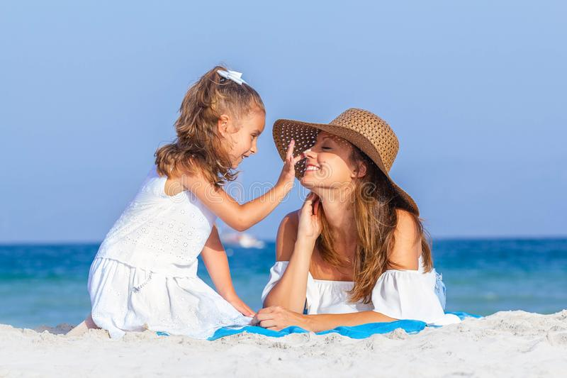 Criança que põe o suncream sobre a cara das mães foto de stock