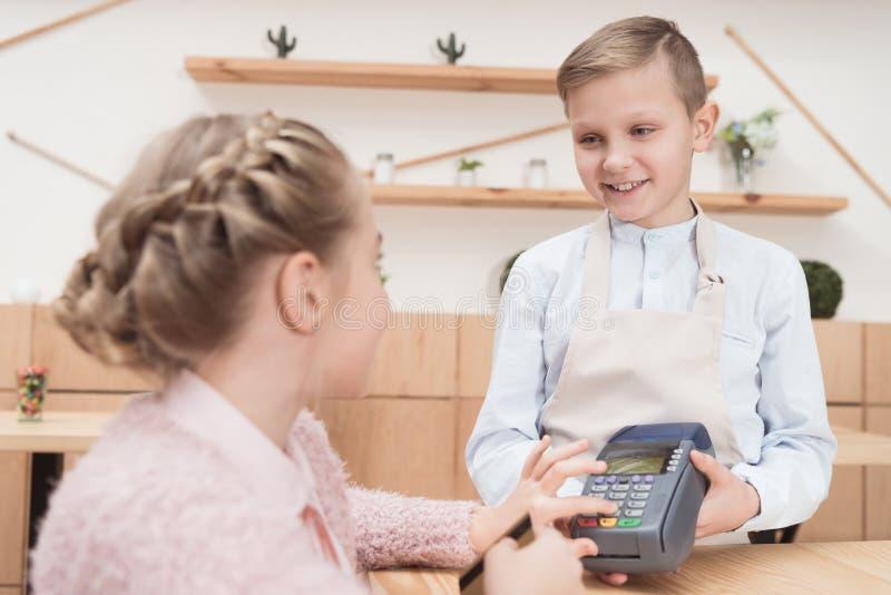 criança que paga pelo cartão de crédito com terminal fotografia de stock