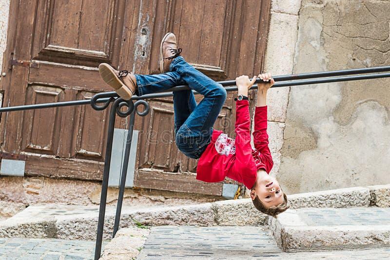 Criança que pendura de uns trilhos na rua Criança que joga na rua foto de stock royalty free