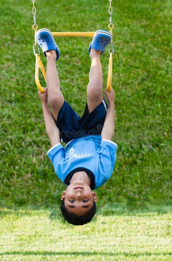 Criança que pendura upside-down em barras de macaco fotos de stock