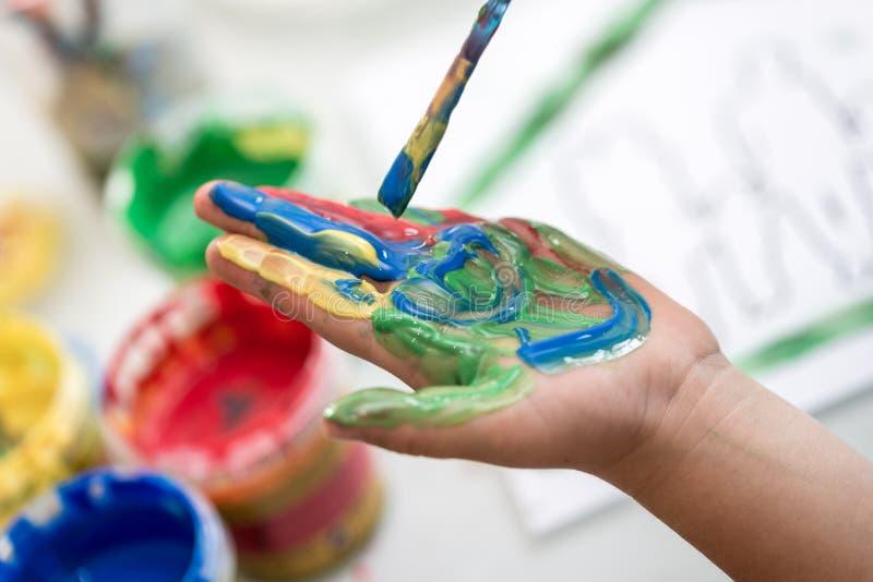 Criança que pinta sua mão com um pincel com pintura colorida imagens de stock