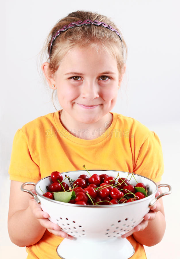 Criança que prende uma bacia de cerejas frescas fotos de stock