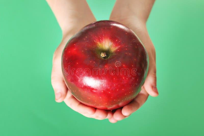 Criança que prende uma maçã vermelha no fundo verde foto de stock