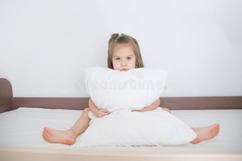 Criança que prepara-se para dormir sentando-se na cama com o descanso no branco imagem de stock royalty free
