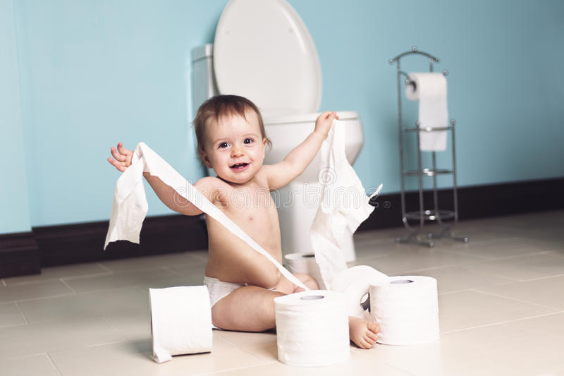 Criança que rasga acima o papel higiênico no banheiro imagens de stock royalty free