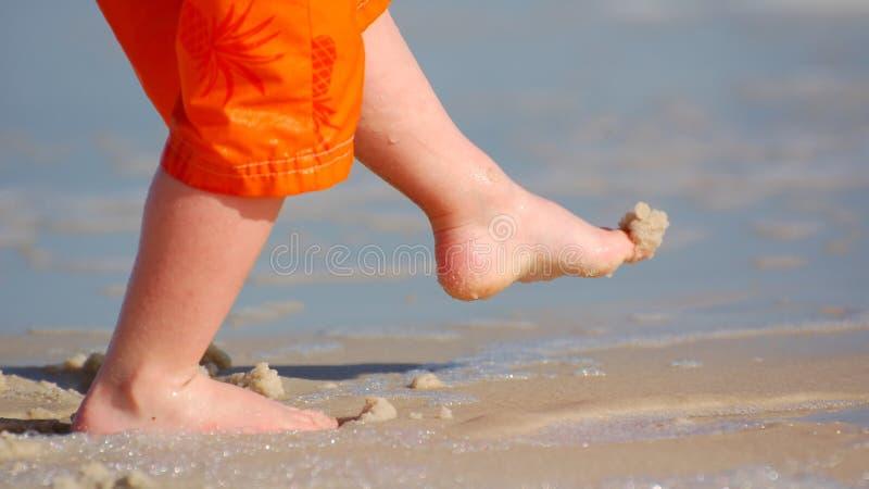 Criança que retrocede a areia imagem de stock royalty free