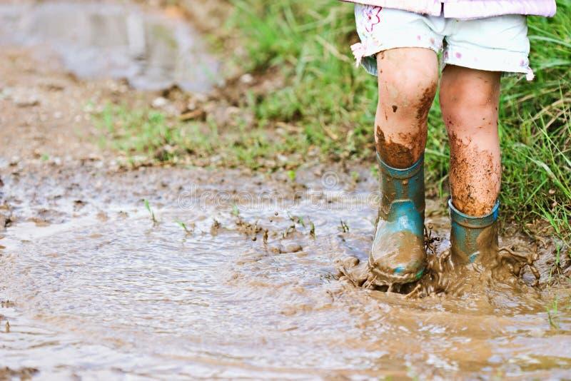 A criança que salta na poça de lama imagens de stock royalty free