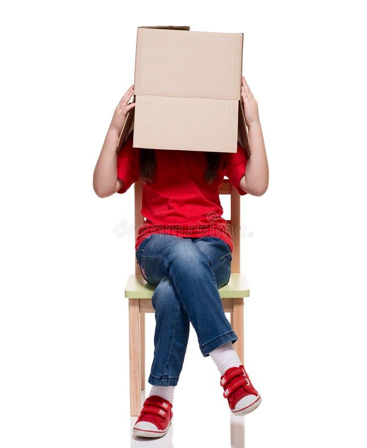 A criança que senta-se em uma cadeira com caixa grande cobriu a cabeça fotos de stock
