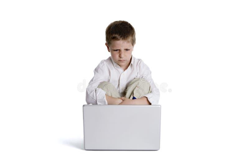Criança que senta-se na frente de um computador portátil fotografia de stock
